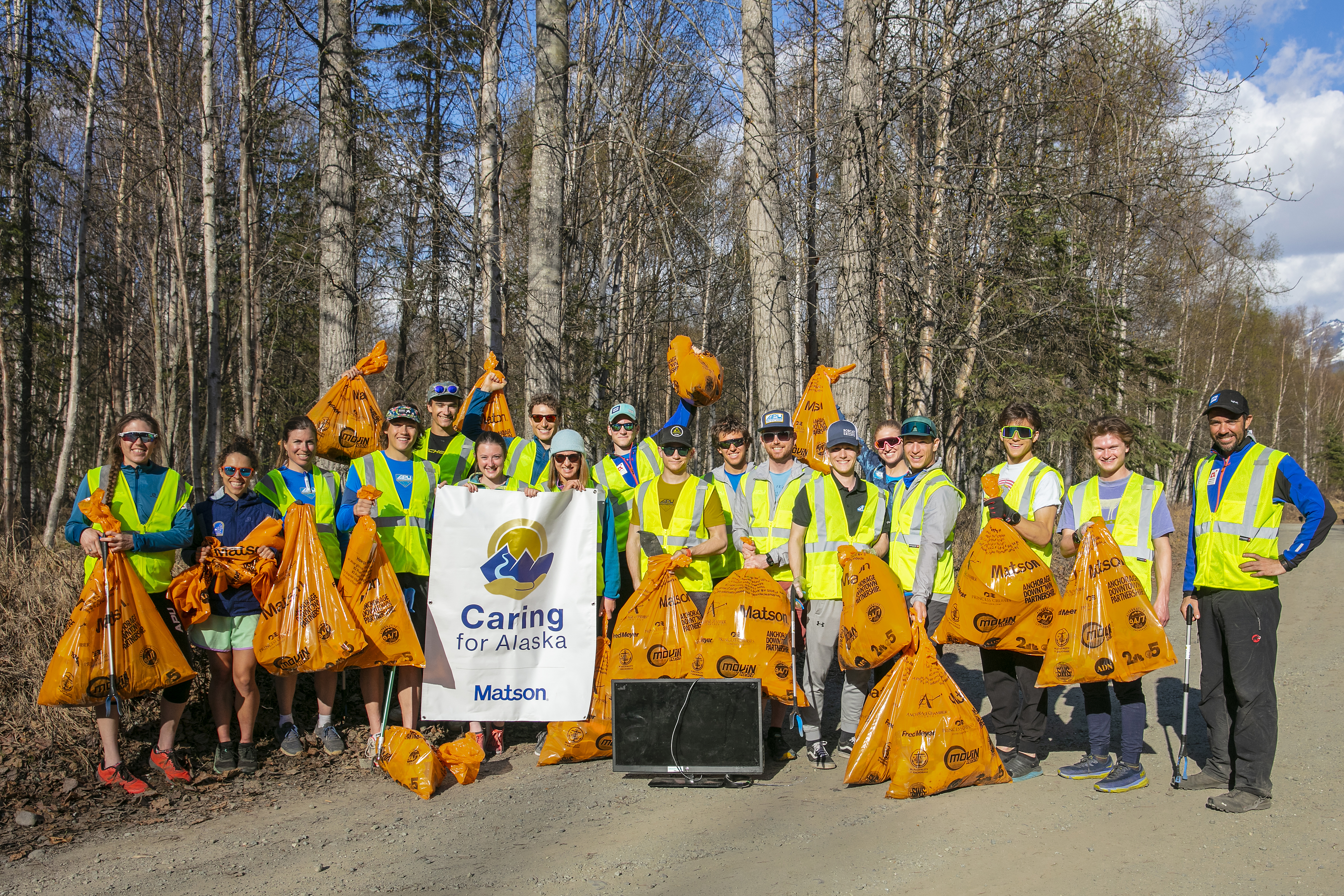 Volunteers wearing yellow safety vests pose for a group picture with their full orange trash bags and Caring For Alaska banner.