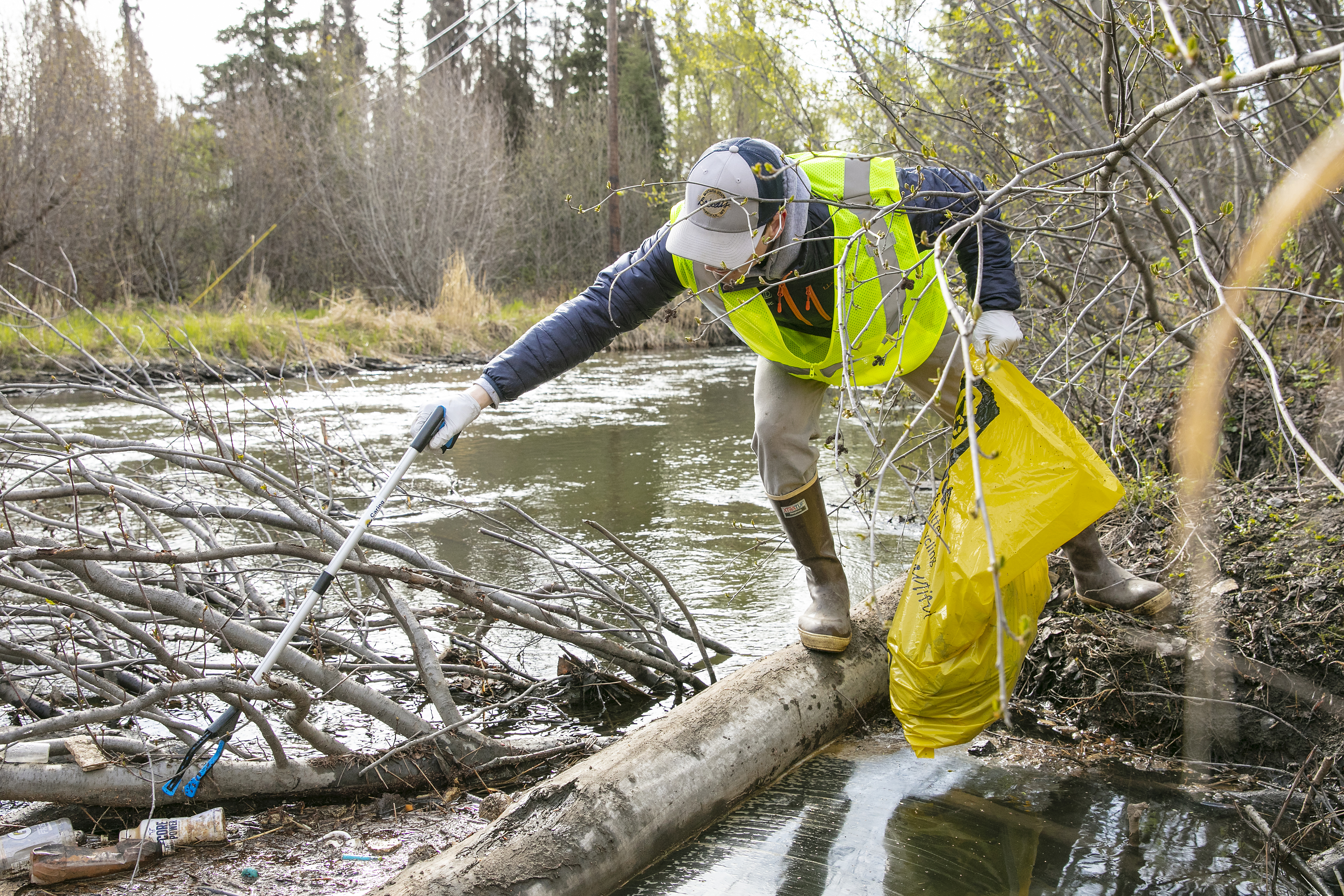 A volunteer wearing rubber boots and yellow safety vest holds a yellow trash bag while reaching with a grabber to pick up trash in Campbell Creek.