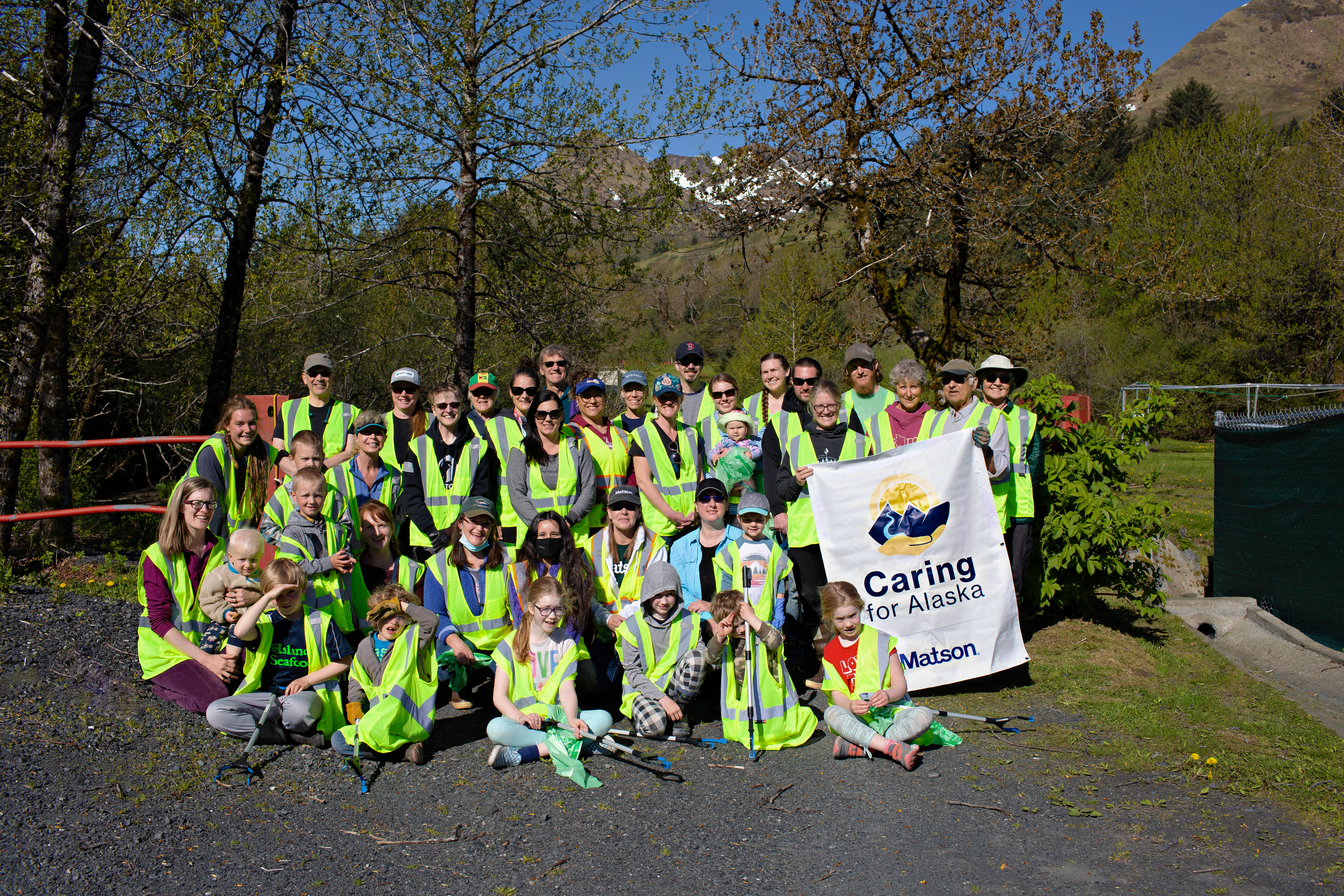 Volunteers wearing their yellow safety vests pose for a group picture with a Caring For Alaska banner.