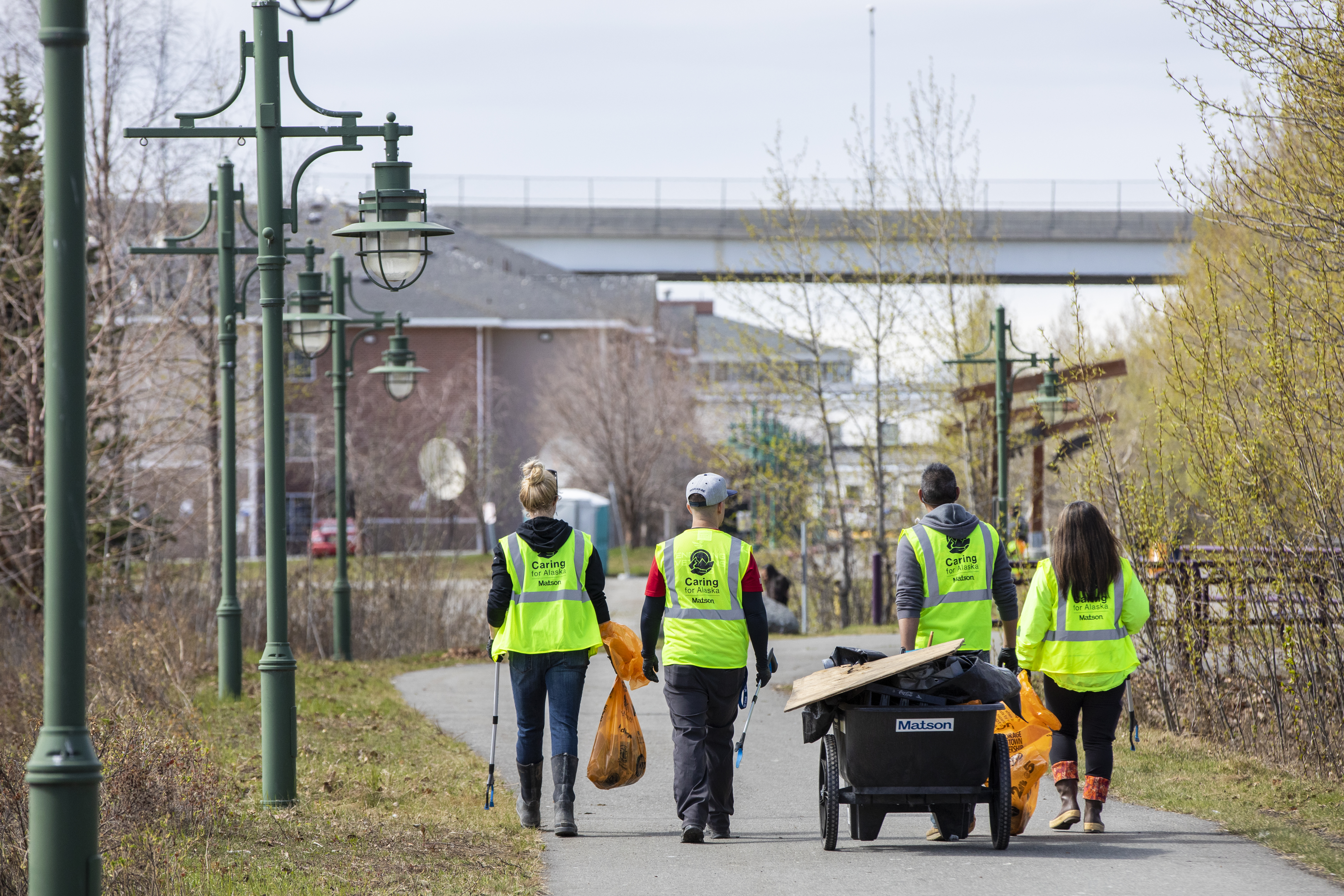 Volunteers wearing yellow safety vests walk along Ship Creek with a cart and orange bags full of trash.