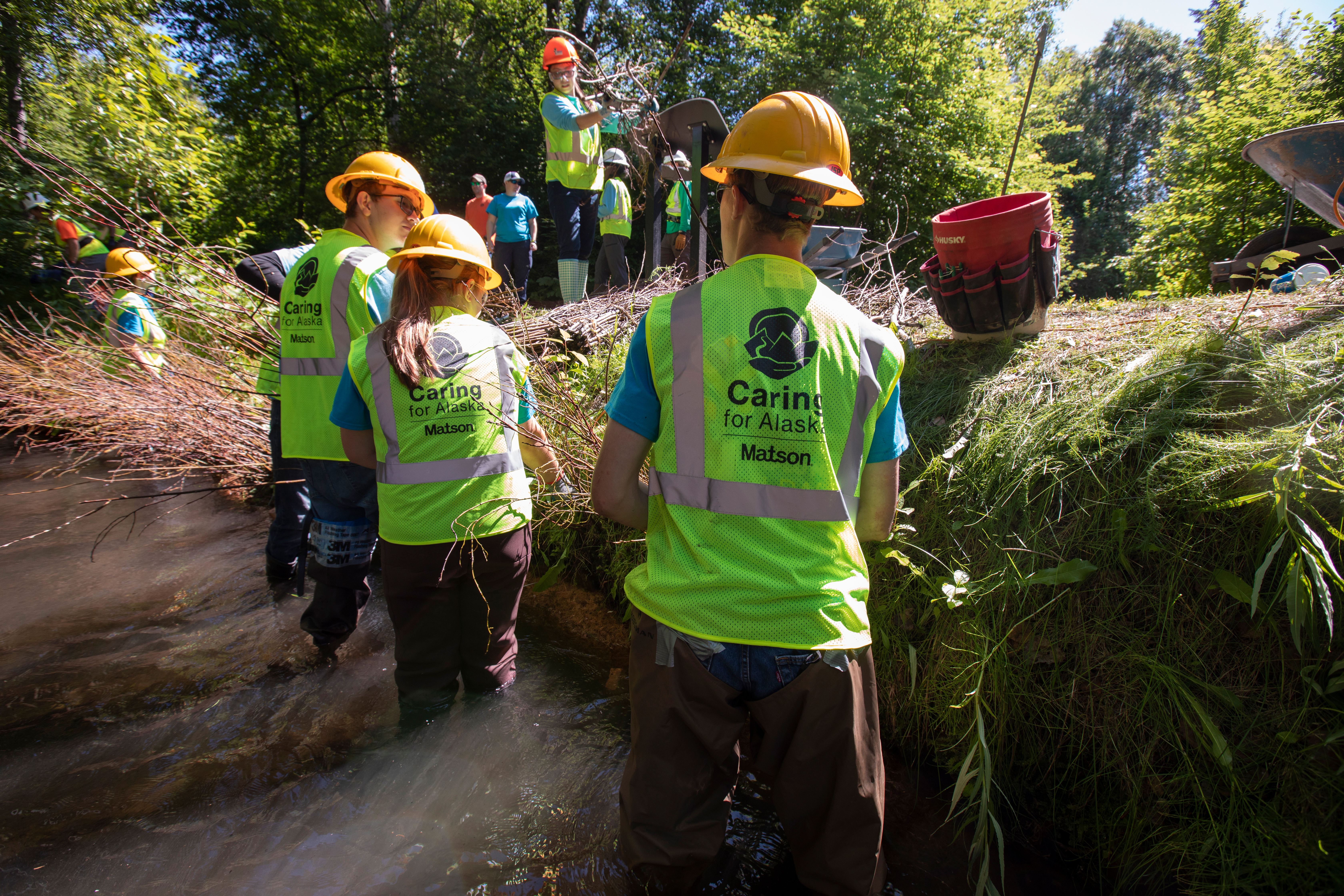 Youth Employment in Parks participants wear green safety vests and yellow hard hats while stand in Chester Creek to remove invasive species and conduct habitat restoration.